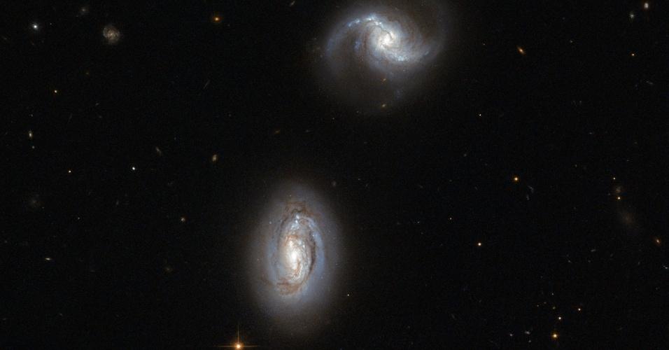 2.jul.2013- Na constelação do Triângulo, a cerca de 2,9 milhões de anos-luz da distância, é possível ver duas galáxias em espiral, atraídas pela gravidade uma da outra. À esquerda da imagem, a galáxia espiral PGC 9074 mostra uma protuberância brilhante e dois braços espirais enrolada ao redor do núcleo; já a PGC 9071 tem uma protuberância mais fraca e uma estrutura ligeiramente diferente para os seus braços, mais afastados. Os braços espirais possuem manchas escuras de poeira que obscurecem a luz das estrelas que estão por trás, com o azul brilhante de estrelas quentes, recém-formadas. Estrelas mais velhas e frias são encontradas no centro amarelado da galáxia. No futuro, prevê-se que as galáxias vão se unir em uma maior