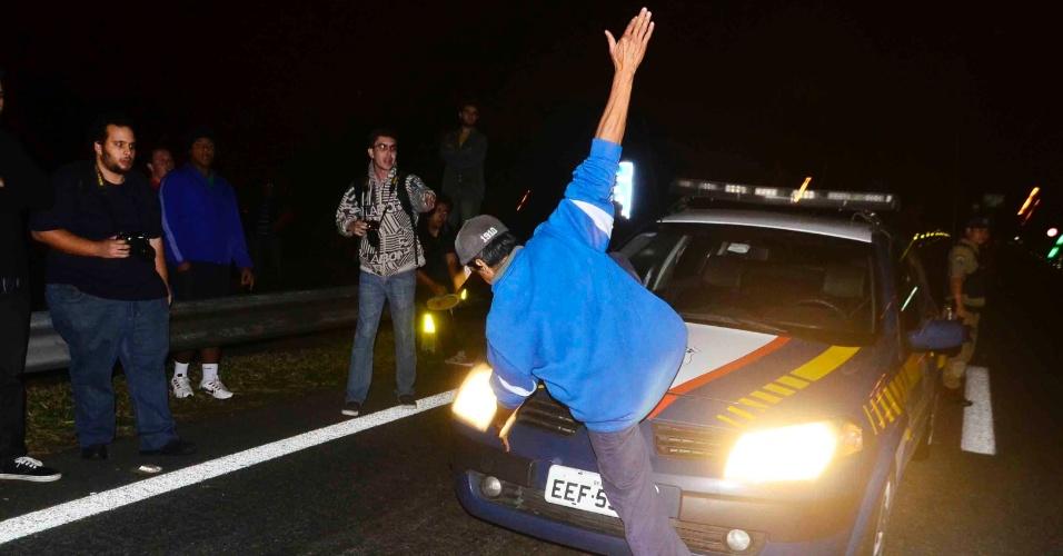 2.jul.2013 - Manifestante chuta carro da Guarda Civil Municiapl que estava parado na Via Dutra, na altura do quilômetro 149, em São José dos Campos (SP). O ato, que pede a revogação do aumento da tarifa do transporte público na cidade, terminou em confronto com a tropa de choque da PM após o grupo bloquear os dois sentidos da via