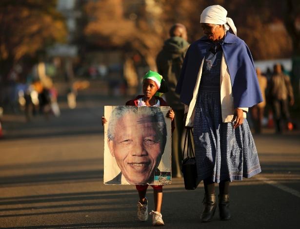 3.jul.2013 - Garoto de 7 anos carrega um cartaz do ex-presidente sul-africano Nelson Mandela. Lehlohonolo Nkosi e a mãe Flora deixaram o Hospital do Coração Mediclinic, onde Mandela está internado há três semanas