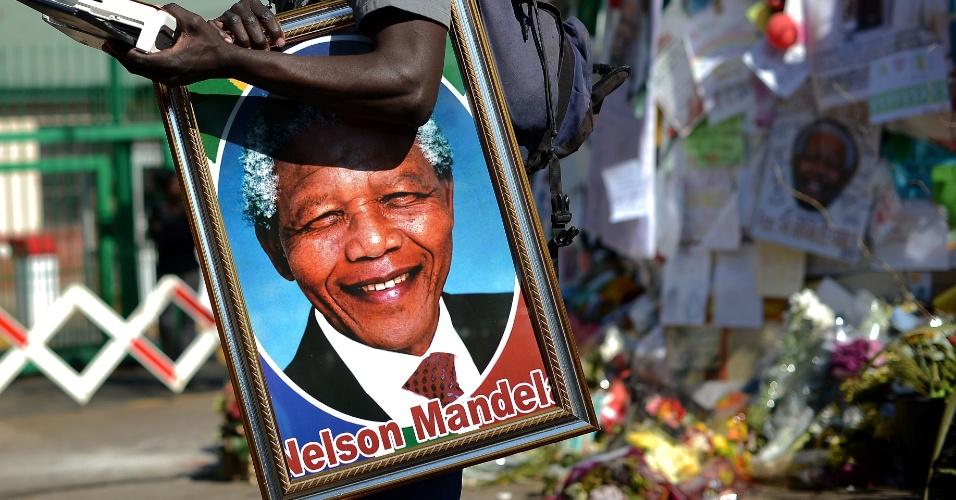 3.jul.2013 - Homem segura um retrato de Nelson Mandela do lado de fora do hospital onde o ex-presidente está internado, em Pretória. Mandela, que completa 95 anos no próximo mês, foi levado às pressas para o hospital há três semanas com um doença pulmonar