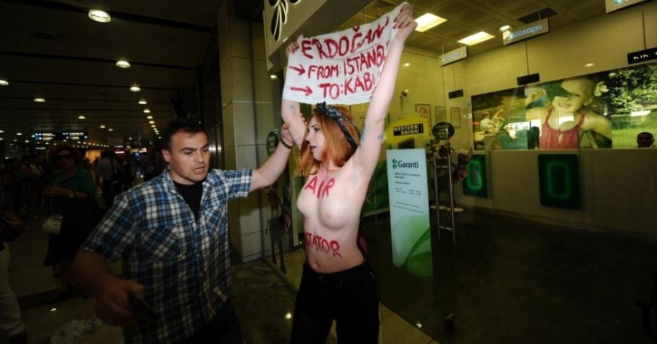 5.jul.2013 - Ativista do Femen (grupo feminista famoso pelos protestos com o uso de topless) realiza manifestação contra o primeiro-ministro turco, Recep Tayyip Erdogan, no aeroporto Sabiha Gokcen, em Istambul, nesta sexta-feira (5)