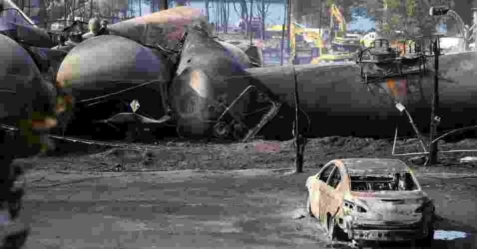 """7.jul.2013 - Carros destruídos fazem parte dos destroços, vistos neste domingo (7), do trem que explodiu enquanto transportava petróleo neste sábado (6), em Lac Megantic, na província de Québec, no Canadá. Segundo a """"Radio Canada"""", o acidente deixou 60 pessoas desaparecidas e 30 prédios destruídos - Christinne Muschi/Reuters"""