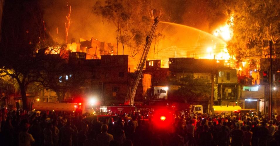 7.jul.2013 - Moradores evacuados observam incêndio de grandes proporções que atinge uma favela na avenida Almirante Delamare, na região de Heliópolis, zona sul de São Paulo