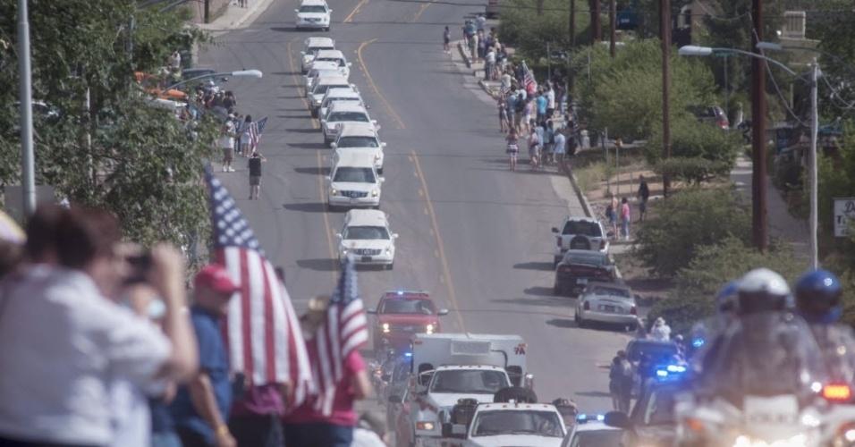 7.jul.2013 - População observa os carros funerários que levam os restos mortais dos 19 bombeiros que morreram durante incêndio em Yarnell, Arizona (EUA). Durante o percurso, parte da multidão prestou homenagem às vítimas com aplausos