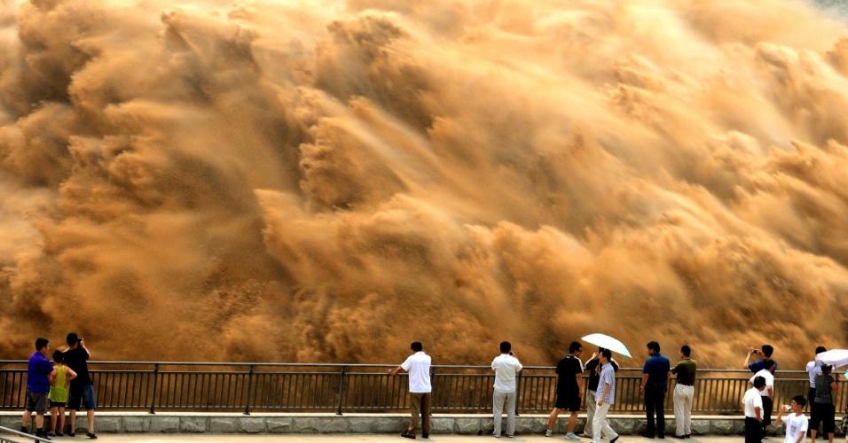 7.jul.2013 - Visitantes assistem água jorrando do reservatório Xiaolangdi, localizado no rio Amarelo, durante uma operação de lavagem da areia em Jiyan, província de Henan, neste domingo (7), na China