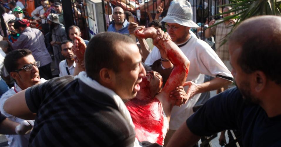 8.jul.2013 - Apoiadores do presidente deposto Mohamed Mursi ajudam a carregar um ferido em mais um episódio de violência no Cairo, capital do Egito. Autoridades confirmaram mais de 40 mortes em um confronto entre as forças do governo provisório e manifestantes pró-Mursi em frente ao quartel-general da Guarda Republicana do país africano