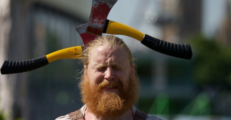 """9.jul.2013 - Artista canadense faz malabarismo com machados na cabeça. O Cirque Alfonse apresenta o espetáculo intitulado """"Madeira!"""" em Londres, Inglaterra"""