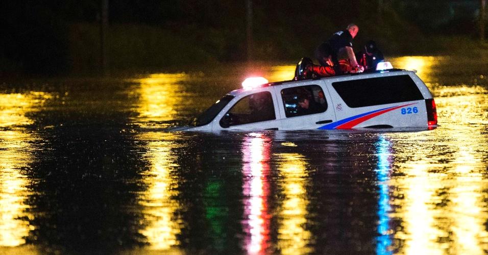 9.jul.2013 - Policiais se ajoelham sobre o teto de jipe da polícia preso em inundação em Toronto (Canadá), ocorrida após forte temporal na cidade nesta segunda-feira (8)