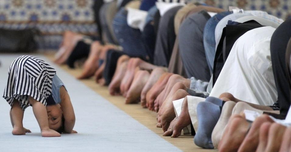 9.julho.2013 - Menino brinca ao lado de fieis orando em mesquita da cidade francesa Estrasburgo