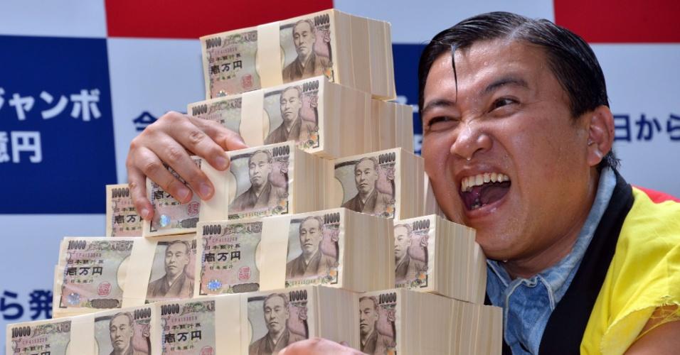 10.jul.2013 - O comediante japonês conhecido como Sugichan posa ao lado de 500 milhões de ienes (R$ 11 milhões) durante o início das vendas de bilhetes da loteria de verão de Tóquio, nesta quarta-feira (10). Milhares de japoneses enfrentaram filas para conseguir fazer apostas no sorteio