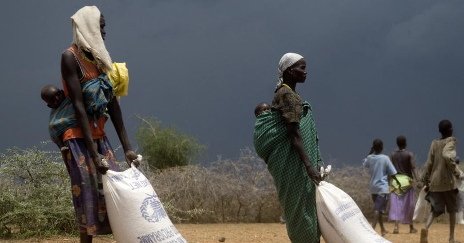 2008: Mulheres de Uganda carregam sacos de comida doados em uma das áreas mais secas e menos desenvolvidas do leste da África. Esta também é uma das áreas mais afetadas pelo aquecimento global e sofre com a falta de alimentos