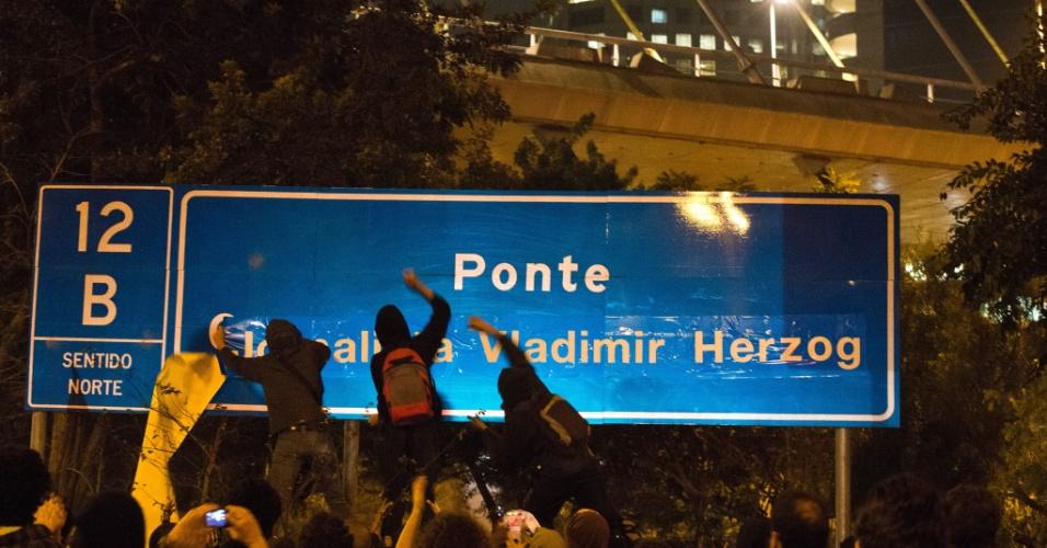 11.jul.2013 - Manifestantes usam adesivo para trocar o nome da ponte estaiada Octavio Frias de Oliveira por jornalista Vladimir Herzog durante protesto na noite desta quinta-feira (11) em frente à sede da Rede Globo, na avenida Engenheiro Luís Carlos Berrini, zona sul de São Paulo. Herzog foi morto durante a ditadura militar. Ele foi encontrado enforcado nas dependências do Destacamento de Operações de Informações - Centro de Operações de Defesa Interna (DOI-Codi) em outubro de 1975, aos 38 anos