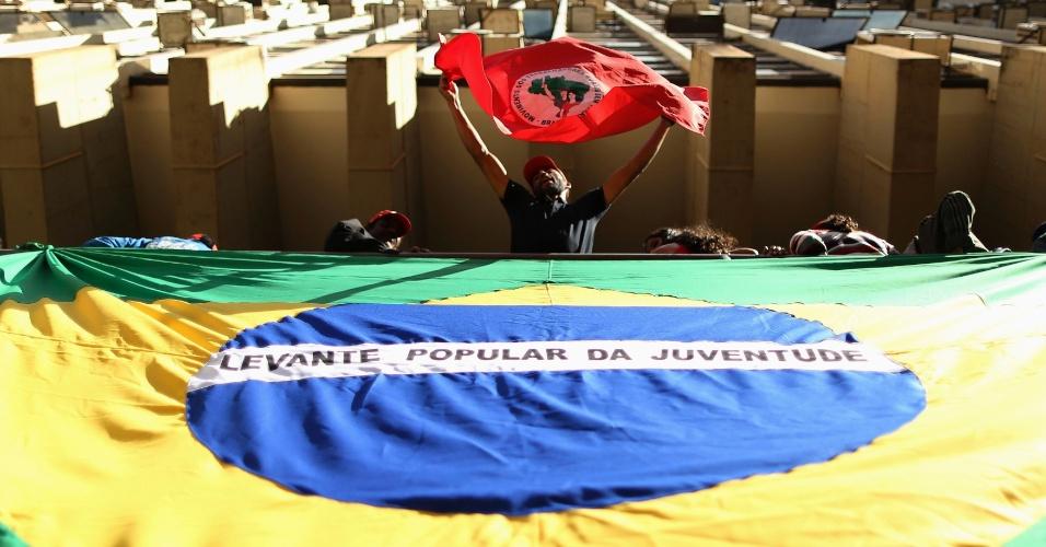 11.jul.2013 - Um membro do MST (Movimento dos Sem-Terra) mostra bandeira do movimento, após ocupar o prédio do Incra (Instituto Nacional de Colonização e Reforma Agrária), em Brasília, nesta quinta-feira. O movimento reivindica a reforma agrária no país