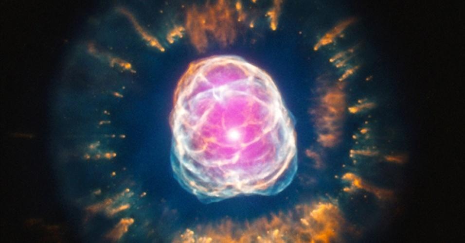 """12.jul.2013 - Estrelas massivas à beira da morte também podem ser fotogênicas. Apesar de ser classificada como uma nebulosa planetária, a NGC 2392 é uma estrela como o nosso Sol em uma fase avançada, já que está se transformando em uma gigante vermelha ao dispensar suas camadas externas (cores vermelhas, verdes e azuis da imagem) e acabando com estoque de hidrogênio do seu núcleo - o Sol ainda vai demorar cerca de 5 bilhões de anos para chegar nesse estágio. Novo registro do Observatório de Raios X Chandra, da Nasa (Agência Espacial Norte-Americana), mostra que a nebulosa do Esquimó, como é apelidada pelos astrônomos, tem bastante gás e plasma muito quente, na ordem dos milhões de graus Celsius, em seu centro (manchas roxas). De acordo com estudo publicado no """"Astrophysical Journal"""", a alta concentração de emissão de raio-x pode indicar a interação de uma estrela binária nessa região localizada a 4.200 anos-luz de distância"""