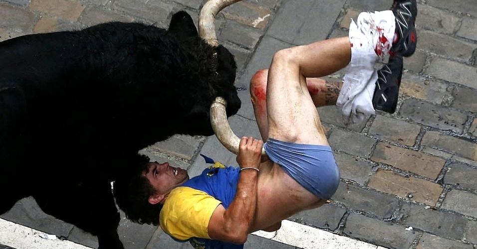 12.jul.2013 - Homem é chifrado na perna por touro na rua Estafeta, durante a sexta corrida dos touros do festival de São Firmino, em Pamplona, nesta sexta-feira (12). Quatro corredores foram atingidos na corrida que teve duração de 4 minutos e 57 segundos, de acordo com a mídia local