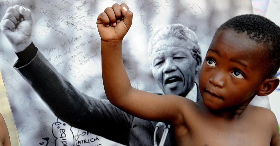apartheid - criança posa para foto em frente a imagem de Nelson Mandela.
