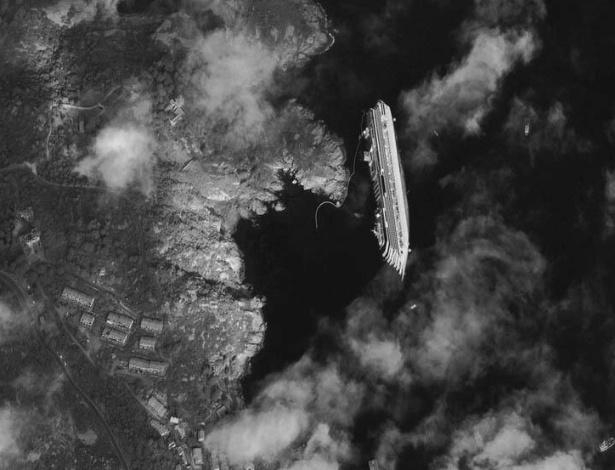17.jul.2013 - Imagem do navio Costa Concordia visto do espaço foi divulgada ontem (16) no Twitter do Google Earth. A embarcação virou perto do porto de Giglio, na Itália em janeiro de 2012, após ter atingido rochas durante uma manobra realizada muito perto da costa. O capitão do navio, cujo acidente matou 32 pessoas, será julgado nesta quarta-feira (17)