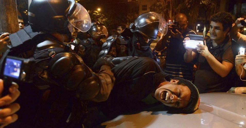 17.jul.2013 - Manifestante é detido pela polícia durante protesto próximo à residência do governador do Rio de Janeiro, Sérgio Cabral (PMDB), na noite desta terça-feira (17)