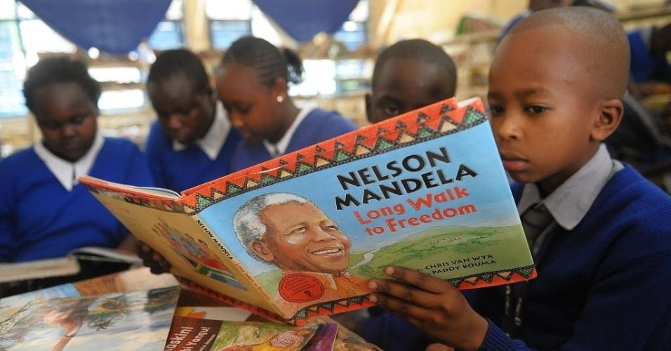 18.jul.2013 - Menino queniano lê livro sobre Nelson Mandela em escola de Nairóbi, no Quênia, nesta quinta-feira (18). O ex-presidente da África do Sul completa 95 anos hoje e recebe homenagens em diversos países da África
