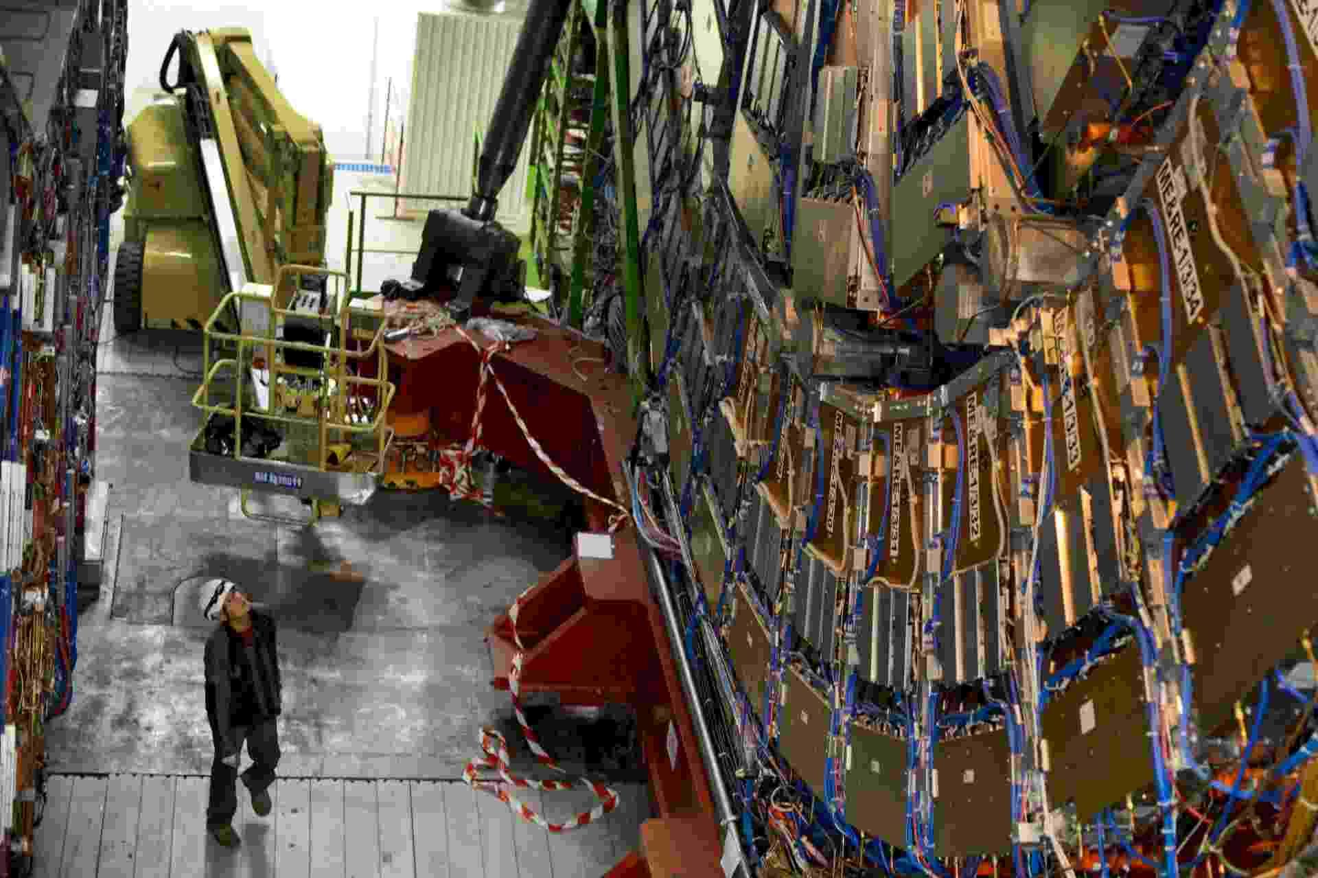"""19.jul.2013 - Homens trabalham na manutenção do Solenoide de Múon Compacto, um dos detectores de partículas do Grande Colisor de Hádrons (LHC, na sigla em inglês), construído no túnel subterrâneo de 27 quilômetros de circunferência do Centro Europeu de Física de Partículas (CERN, na sigla em francês), na fronteira entre a Suíça e a França. O maior acelerador de partículas do mundo está, desde fevereiro de 2013, em manutenção e deverá ficar """"desligado"""" por dois anos - Fabrice Coffrini/AFP"""