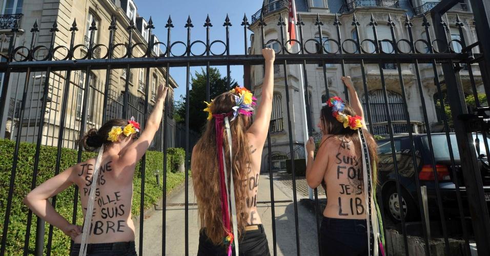22.jul.2013 - Integrantes do grupo feminista Femen protestam seminuas em frente à embaixada da Tunísia em Bruxelas, na Bélgica, nesta segunda-feira (22), após trancar o portão do local. Elas reivindicam a libertação da ativista tunisiana Amina Tyler, detida na cidade. Amina foi presa na Tunísia em maio por pichar o nome do grupo em uma parede na cidade de Kairouan e por causar escândalo em seu país ao postar fotos suas de topless na internet