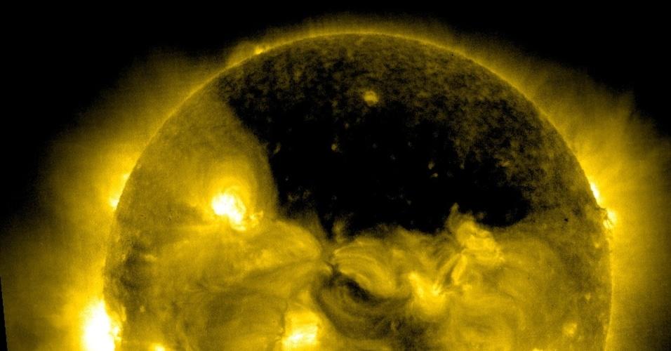 22.jul.2013 - Um buraco coronal gigantesco sobre a região do polo Norte do Sol foi captado pelo Observatório Solar Heliosférico (SOHO, na sigla em inglês) no dia 18 de julho, às 09h06 EDT (às 10h06, no fuso de Brasília). Os buracos coronais são, na verdade, regiões escuras e de baixa densidade que surgem na atmosfera mais externa do Sol, a corona: como há pouco material solar e temperatura muito fria, eles parecem ser bem mais escuros do que o ambiente ao seu redor, explica a Nasa (Agência Espacial Norte-Americana)