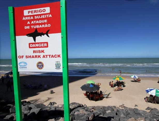 Movimentação na praia de Boa Viagem. Placa avisa, claramente, sobre riscos de ataque de tubarão