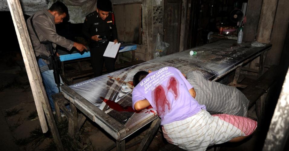 23.jul.2013 - Policiais tailandeses inspecionam os corpos de dois muçulmanos suspeitos de serem baleados por militantes separatistas da província de Narathiwat, no sul do país. A violência é comum nesta região da Tailândia, de maioria muçulmana, e onde moradores se queixam de discriminação pelas autoridades do país, majoritariamente budista