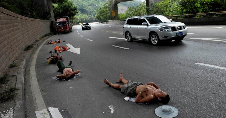 23.jul.2013 - Trabalhadores de local próximo descansam em estrada enquanto carros passam ao lado, na cidade de Chongqing, centro-sul da China