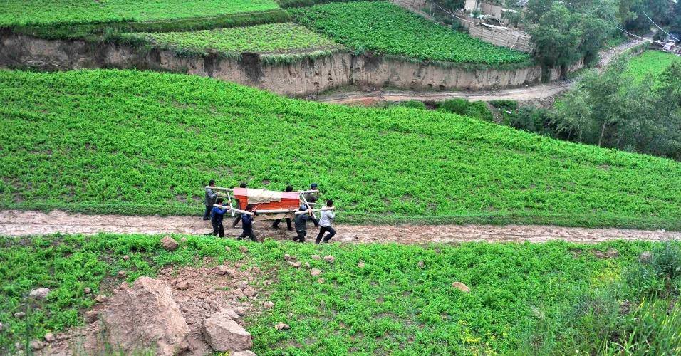24.jul.2013 - Moradores de vilarejo na região de Minxian, no centro da China, carregam caixão de vítima do terremoto que atingiu o país na manhã desta terça-feira (23). Ao menos 95 pessoas morreram em decorrência do tremor, que ainda feriu outras 500, e causou o desabamento de ao menos 1.200 edifícios. As autoridades lutam para que as chuvas que atingem o país há semanas não causem ainda mais danos, Imagem divulgada nesta quarta-feira (24)