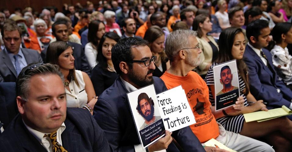 24.jul.2013 - Defensores do fechamento da detenção na base naval americana na Baía de Guantánamo, em Cuba, seguram fotos de prisioneiros enquanto assistem a uma audiência do Comitê Judiciário do Senado, em Washington, capital dos Estados Unidos, nesta quarta-feira (24). Parlamentares ouviram depoimentos de testemunhas durante apresentação de um painel