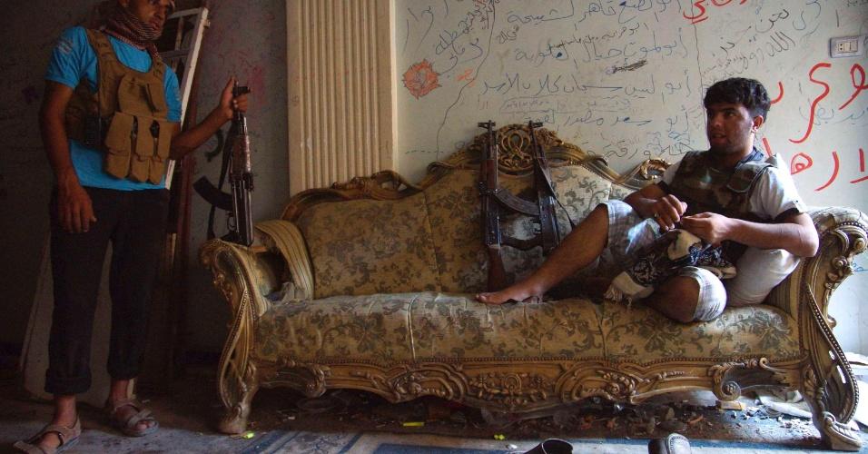 24.jul.2013 - Em de terça-feira (23), divulgada nesta quarta (24), soldado do Exército Síria Livre descansa em sofá ao lado companheiro, em casa na cidade de Deir al-Zor