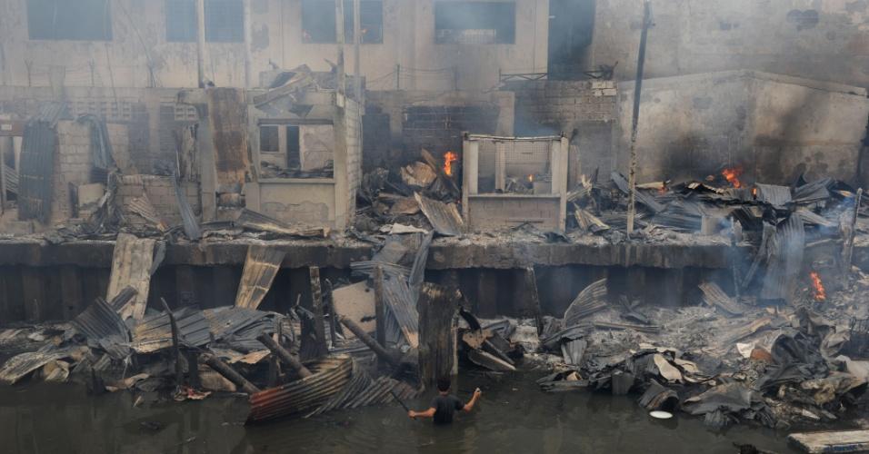 24.jul.2013 - Filipino tenta recuperar pertences após incêndio destruir uma favela, nesta quarta-feira (24), em Manila, nas Filipinas. Cerca de 200 casas foram consumidas pelas chamas, e mais de 400 pessoas estão desabrigadas