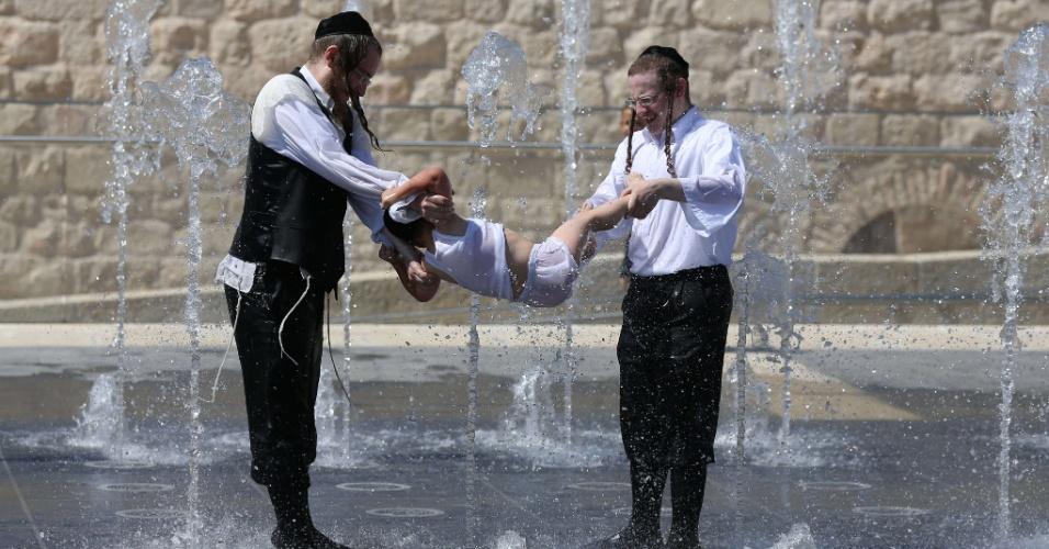 24.jul.2013 - Judeus ortodoxos se refrescam em uma fonte na cidade de Jerusalém, nesta quarta-feira (24). O período de férias, conhecido com Bein Hazmanim, coincide com o verão em Israel