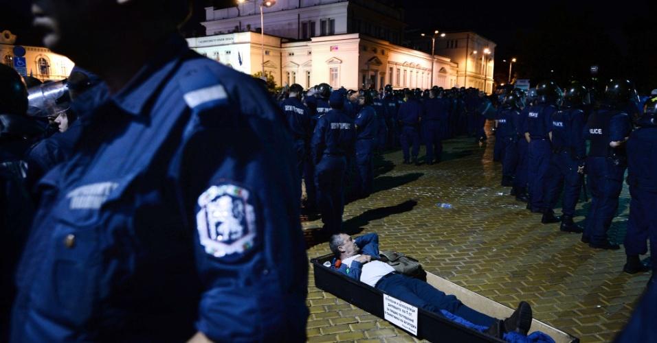 24.jul.2013 - Manifestante se deita em caixão na frente de policiais búlgaros que abrem caminho para a saída de legisladores e assessores do Parlamento da Bulgária, em Sófia, na madrugada desta quarta-feira (24). Ministros, parlamentares e jornalistas passaram mais de 5 horas trancados dentro do edifício após protestos contra o governo do país mais pobre da UE