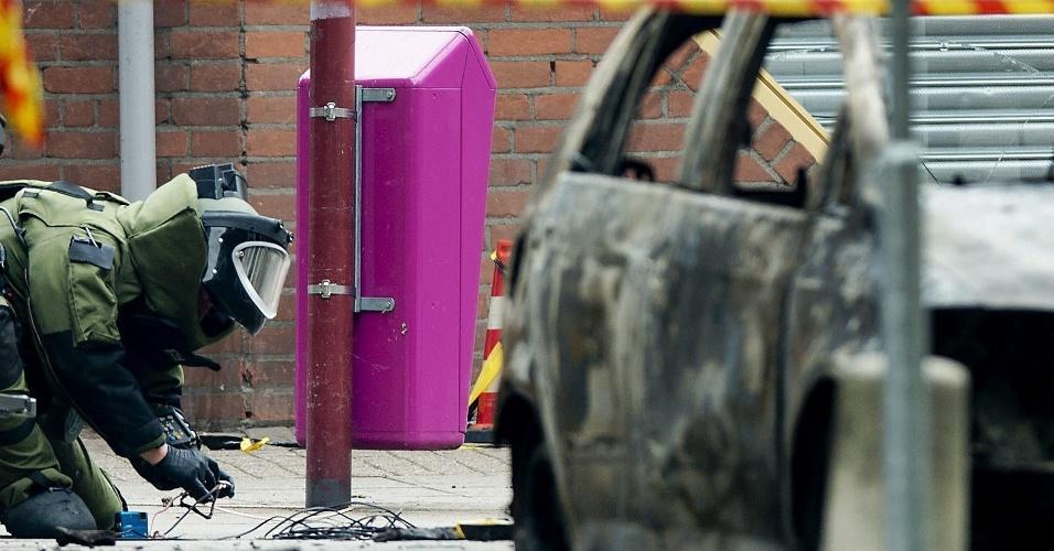 24.jul.2013 - Policial examina destroços de um carro danificado por uma bomba, nesta quarta-feira (24), em Nieuwegein, na Holanda. O artefato foi descoberto antes da detonação atrás de um caixa automático, e as autoridades tiveram tempo de esvaziar o local