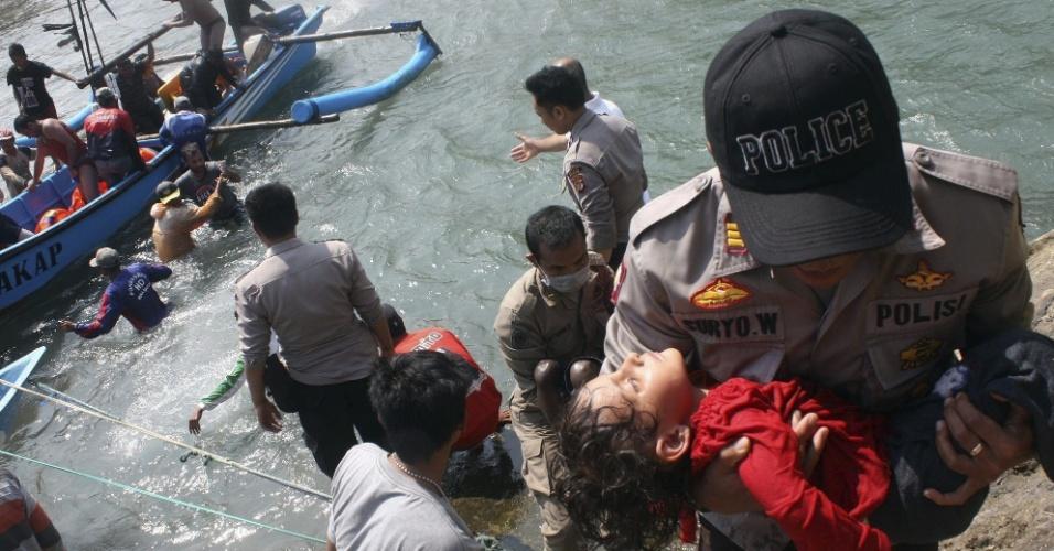24.jul.2013 - Policial indonésio carrega menino no colo durante operação de resgate de sobreviventes de um naufrágio, nesta quarta-feira (24), em Cidaun. Pelo menos três pessoas morreram. A embarcação levava cerca de 200 imigrantes para a Austrália