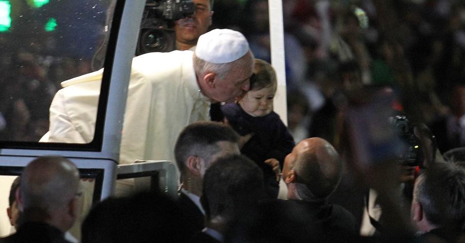 25.jul.2013 - Criança é beijada pelo papa Francisco durante percurso até o palco montado na praia de Copacabana, nesta quinta-feira (25), durante celebração da JMJ (Jornada Mundial da Juventude) 2013