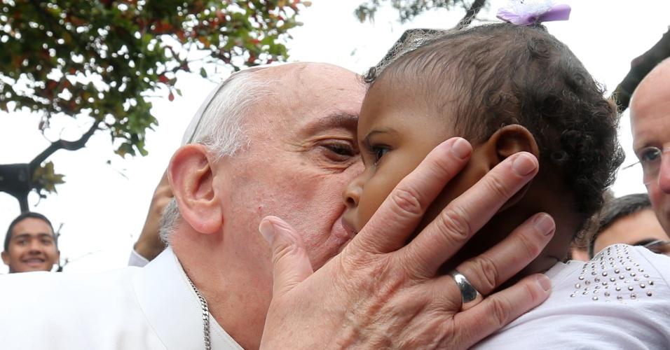 25.jul.2013 - Papa Francisco beija bebê durante visita à favela Varginha, no Complexo de Manguinhos, zona norte do Rio, nesta quinta-feira