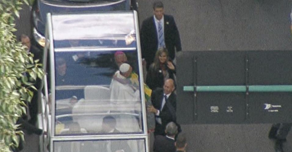 26.jul.2013 - O papa Francisco abraça uma criança enquanto se desloca de papamóvel pelas ruas do Rio de Janeiro