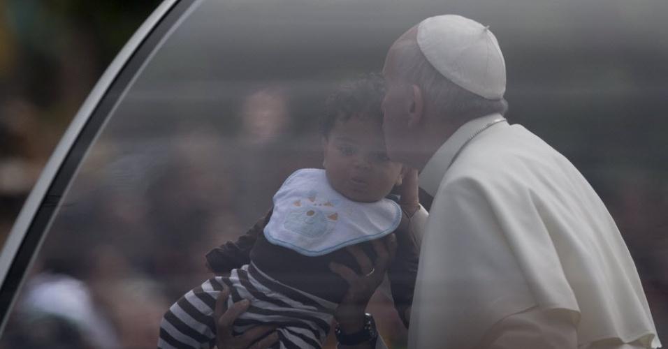 26.jul.2013 - O papa Francisco beija uma criança enquanto se desloca de papamóvel pelas ruas do Rio de Janeiro