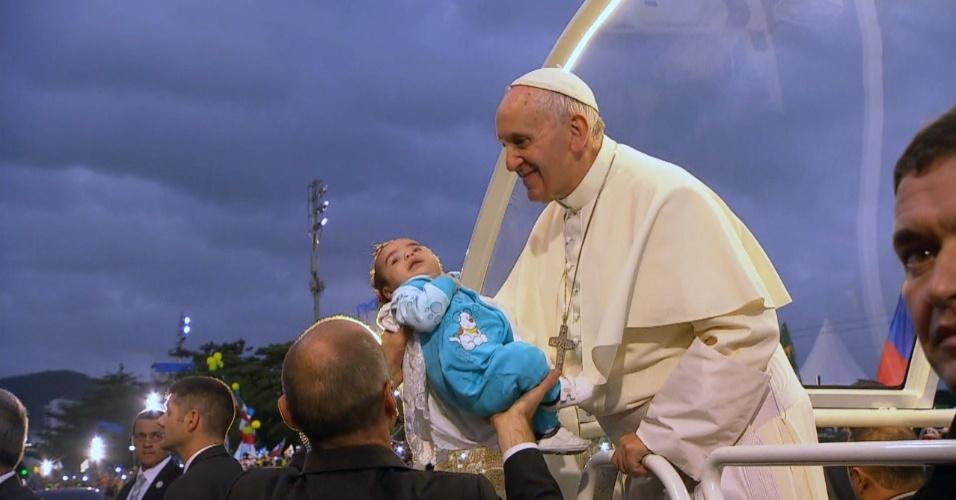 26.jul.2013 - Papa Francisco abençoa criança enquanto anda de papamóvel pelas ruas de Copacabana. O pontífice segue rumo ao palco localizado no bairro, onde haverá a encenação da Via Sacra