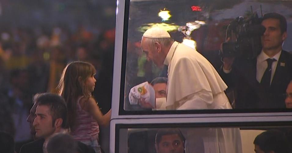 26.jul.2013 - Papa Francisco recebe presente de criança enquanto anda de papamóvel pelas ruas de Copacabana. O pontífice segue rumo ao palco localizado no bairro, onde haverá a encenação da Via Sacra