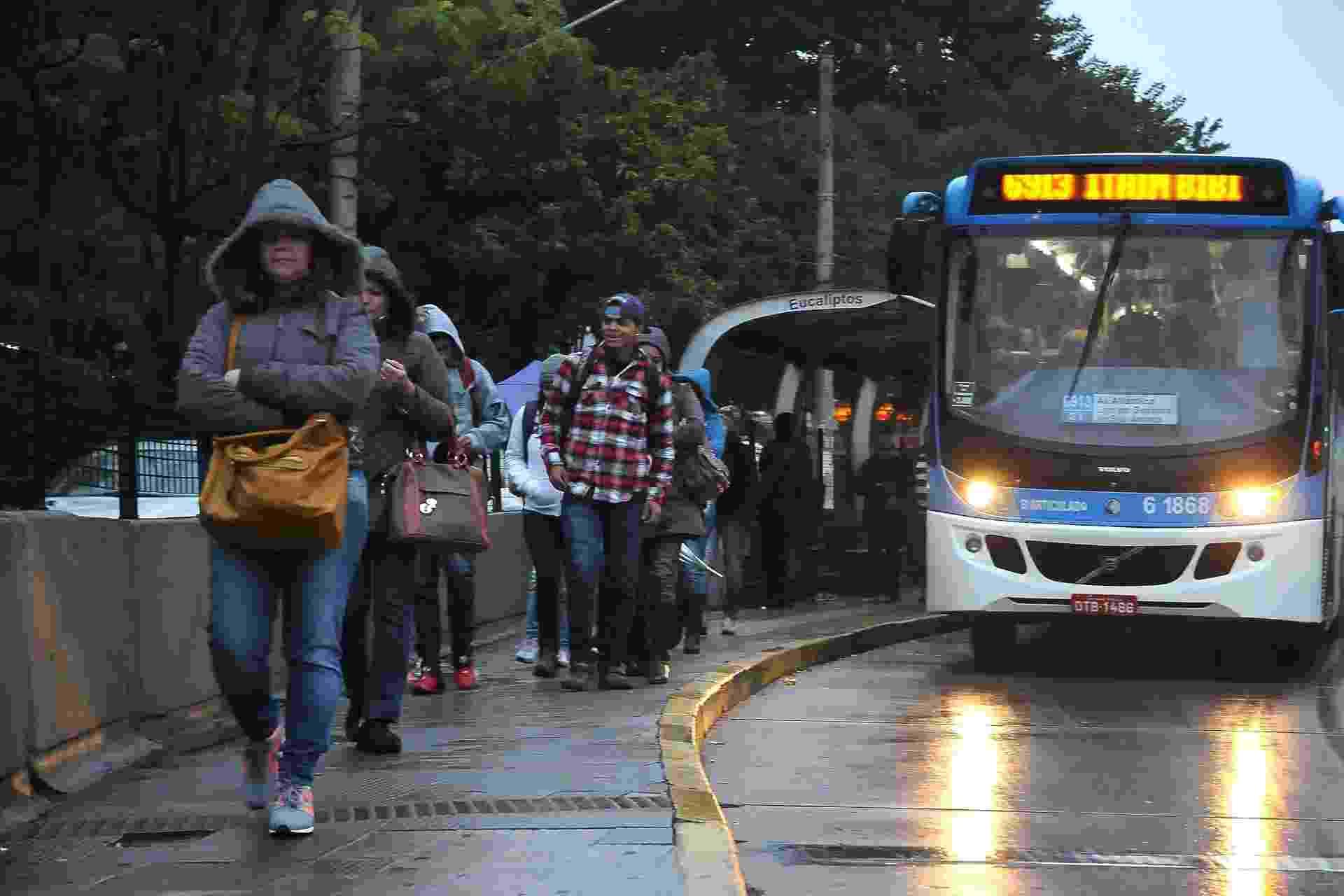 26.jul.2013 - Pedestres enfrentam manhã fria e chuvosa à espera de ônibus na avenida Santo Amaro, na zona sul de São Paulo - Felipe Andrei/Futura Press