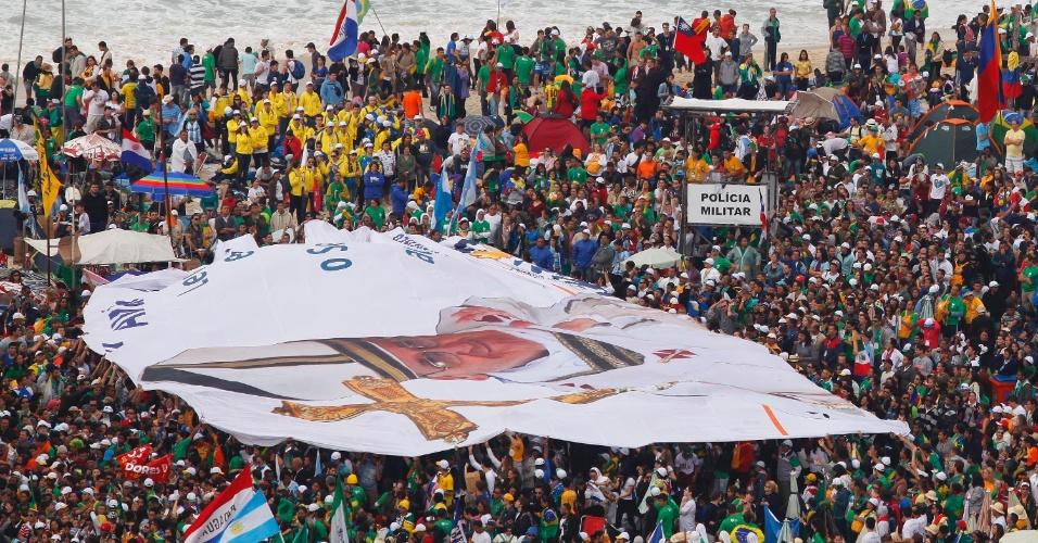 28.jul.2013 - Bandeira gigante com foto do papa Francisco é erguida por peregrinos na praia de Copacabana antes da missa de encerramento da JMJ (Jornada Mundial da Juventude)