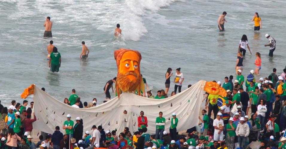 28.jul.2013 - Boneco que representa Cristo de braços abertos é erguido por peregrinos na praia de Copacabana antes da missa do papa Francisco, de encerramento da JMJ (Jornada Mundial da Juventude)