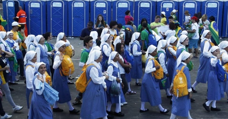 28.jul.2013 - Grupo de freiras passa por banheiros químicos nos arredores de Copacabana, na Jornada Mundial da Juventude no Rio de Janeiro. Mais de 3 milhões de fiéis, a maioria jovens brasileiros e latino-americanos, participaram da missa final do evento, segundo Frederico Lombardi, porta-voz da Santa Sé
