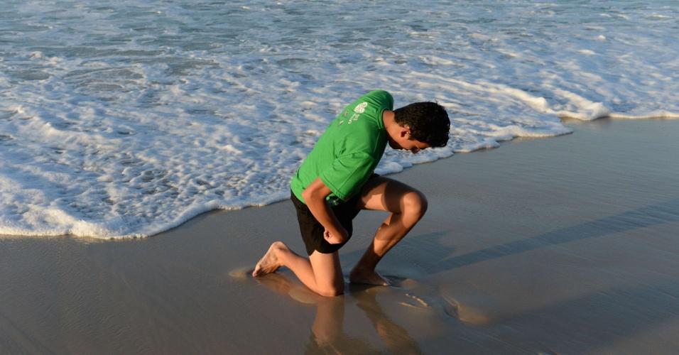 28.jul.2013 - Jovem se ajoelha na praia de Copacabana enquanto o papa Francisco celebra missa de encerramento da JMJ (Jornada Mundial da Juventude), na praia de Copacabana, no Rio de Janeiro