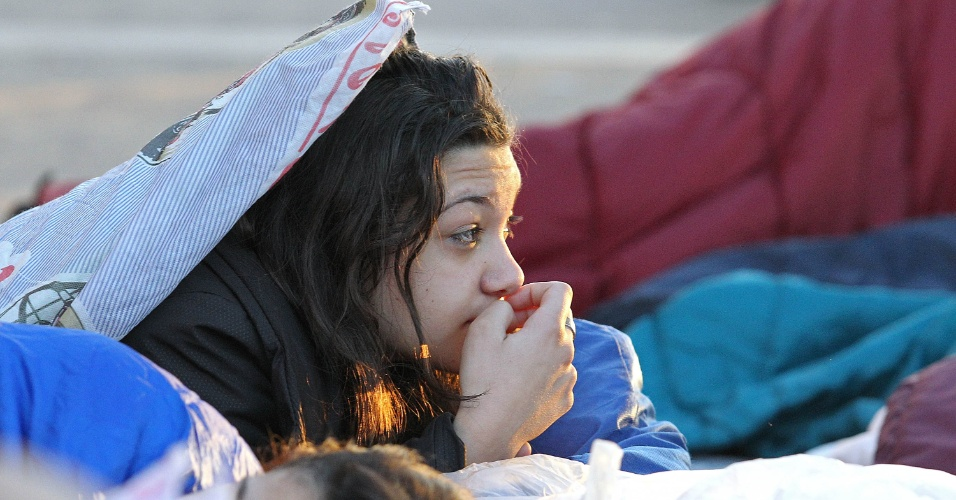 28.jul.2013 - No último dia da Jornada Mundial da Juventude, peregrinos que participaram da vigília do papa Francisco acordam após passarem a noite na praia de Copacabana, no início da manhã deste domingo (28)