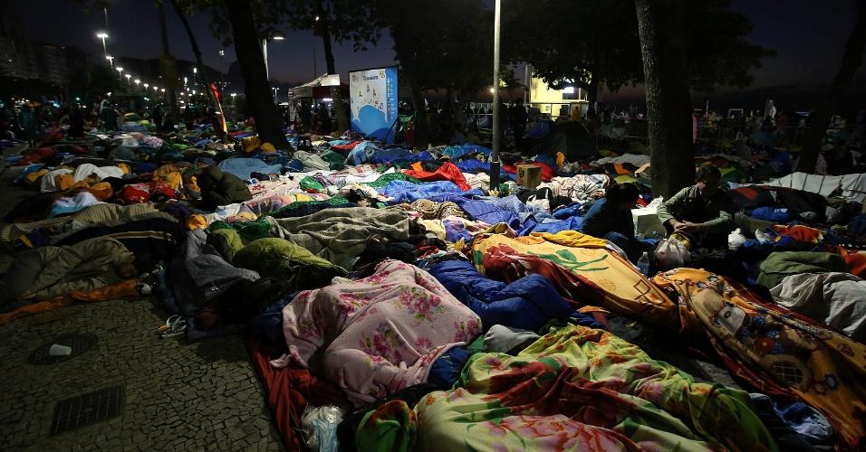 28.jul.2013 - No último dia da Jornada Mundial da Juventude, peregrinos que participaram da vigília do papa Francisco dormiram nas ruas e na areia da praia de Copacabana, no início da manhã deste domingo (28)